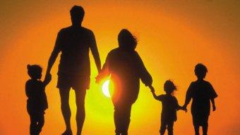 Ģimene uz saulrieta fona